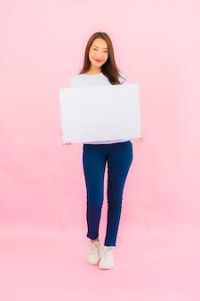 La bella giovane donna asiatica del ritratto mostra il tabellone per le affissioni bianco vuoto per testo sulla parete di colore rosa