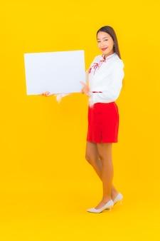 肖像画の美しい若いアジア女性は、分離された黄色の白い空の看板を表示します。