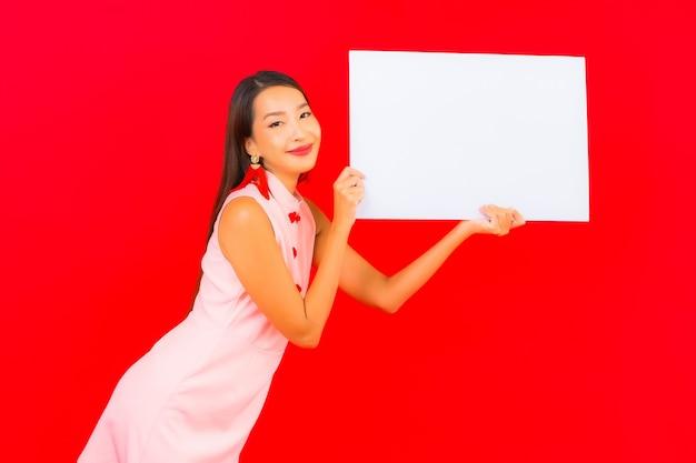 La bella giovane donna asiatica del ritratto mostra il tabellone per le affissioni vuoto bianco sulla parete rossa