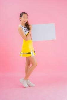 肖像画の美しい若いアジア女性は白い空の看板を表示します