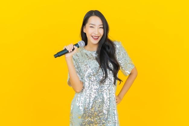 La bella giovane donna asiatica del ritratto canta una canzone con il microfono su colore giallo