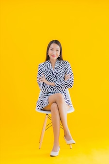 Portrait beautiful young asian woman sit on chair with action on yellow