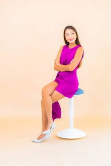 Portrait beautiful young asian woman sit on chair with color background