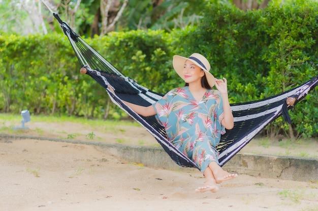 La bella giovane donna asiatica del ritratto si siede sull'oscillazione dell'amaca intorno all'oceano del mare della spiaggia in vacanza di festa