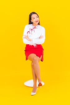 세로 아름 다운 젊은 아시아 여자 노란색에의 자에 앉아