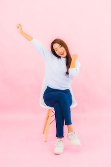 肖像画美しい若いアジアの女性がピンク色の壁と椅子に座っ