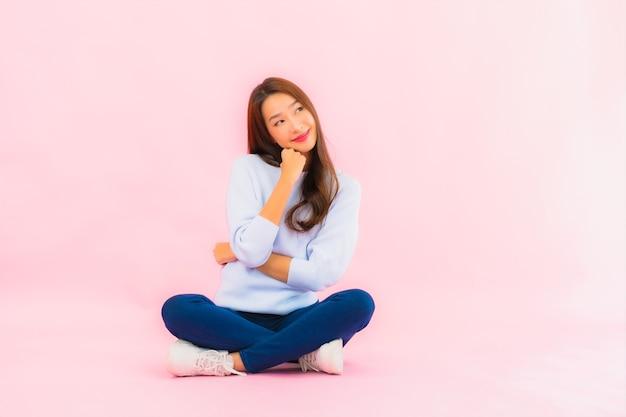 肖像画美しい若いアジアの女性がピンク色の孤立した壁と床に座る