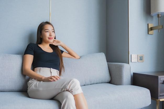 ソファの上に座って美しい若いアジア女性の肖像画はリビングルームエリアでリラックスします。