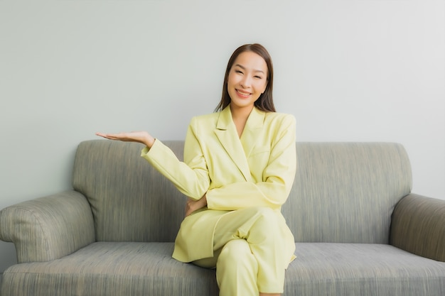 Portrait beautiful young asian woman sit with smile on sofa in living room interior