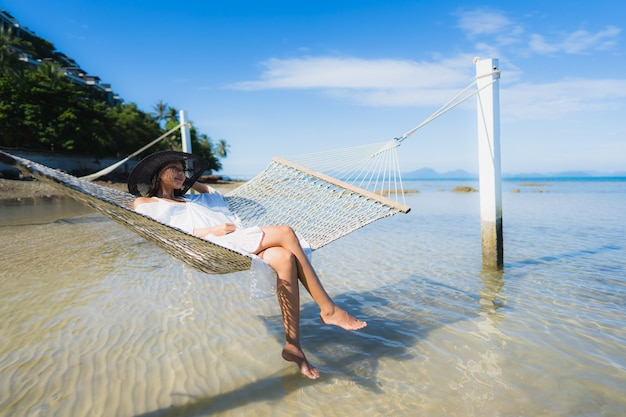 Portrait beautiful young asian woman sitting on hammock around sea beach ocean for relax