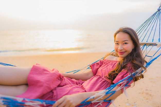 Portrait beautiful young asian woman sitting on the hammock with smile happy neary beach sea and oce