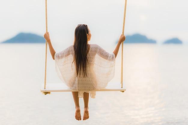 リラックスのために海の海の周りのブランコに座っている肖像画美しい若いアジア女性