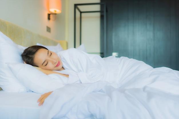 肖像画の美しい若いアジア女性は枕と毛布が付いているベッドで寝る