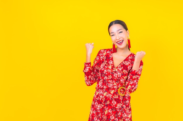 Portrait beautiful young asian woman smile in action in chinese new year concept on color wall