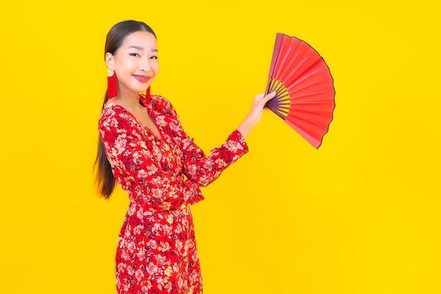 Sorriso della bella giovane donna asiatica del ritratto nell'azione nel concetto cinese del nuovo anno sulla parete di colore