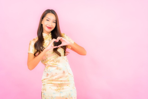 Portrait beautiful young asian woman smile in action with chinese new year concept on pink color wall