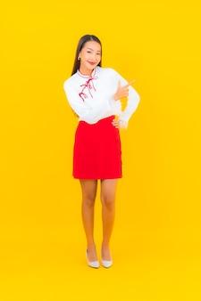 Ritratto bella giovane donna asiatica sorriso in azione su yellow