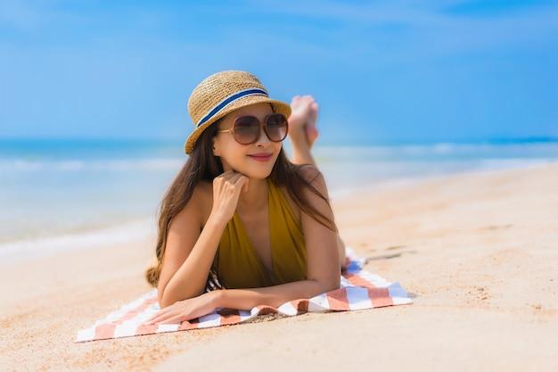 초상화 아름 다운 젊은 아시아 여자는 해변과 바다에 행복 미소