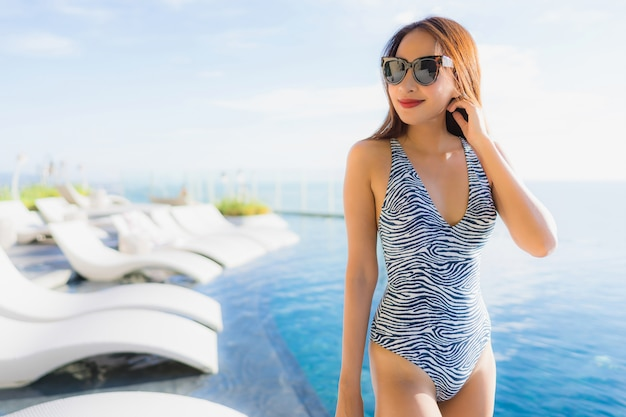 Portrait beautiful young asian woman smile happy relax around swimming pool in hotel resort for leisure