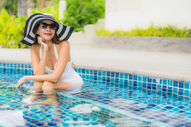 Portrait beautiful young asian woman smile happy relax around swimming pool in hotel resort