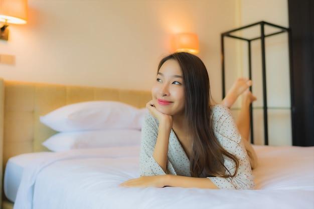 Il sorriso felice della bella giovane donna asiatica del ritratto si rilassa sul letto