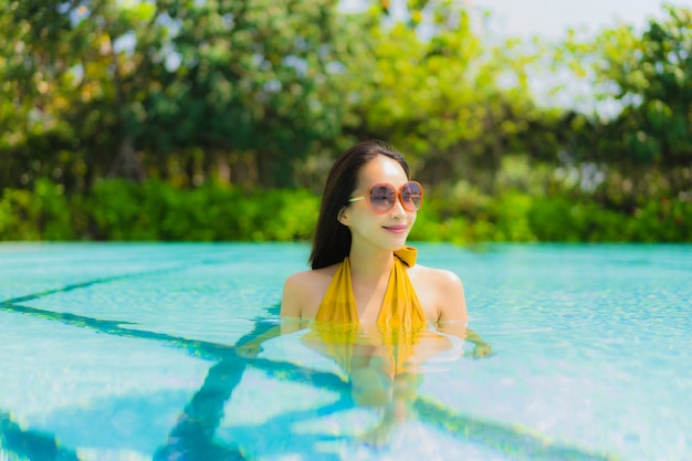 Portrait beautiful young asian woman smile happy relax and leisure in the swimming pool