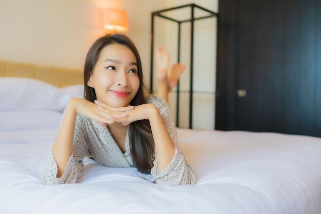 Улыбка красивой молодой азиатской женщины портрета счастливая ослабляет на кровати