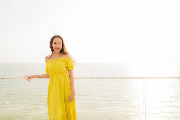 Portrait beautiful young asian woman smile happy and relax at outdoor balcony with sea beach and oce