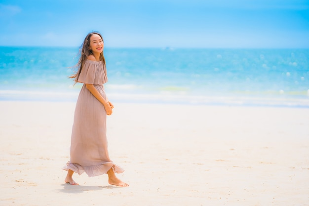 Portrait beautiful young asian woman smile happy walk on the tropical outdoor nature beach sea