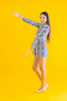 Portrait beautiful young asian woman smile happy with action on yellow