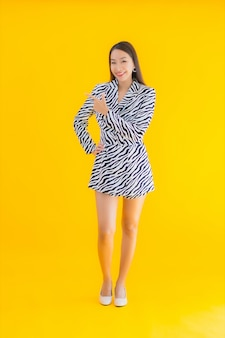 Bello giovane sorriso asiatico della donna del ritratto soddisfatto di azione su giallo