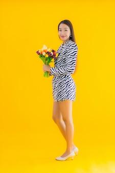 肖像画の美しい若いアジア女性は黄色の花に満足して笑顔します。