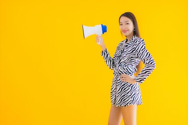 肖像画の美しい若いアジア女性は黄色のメガホンに満足して笑顔します。
