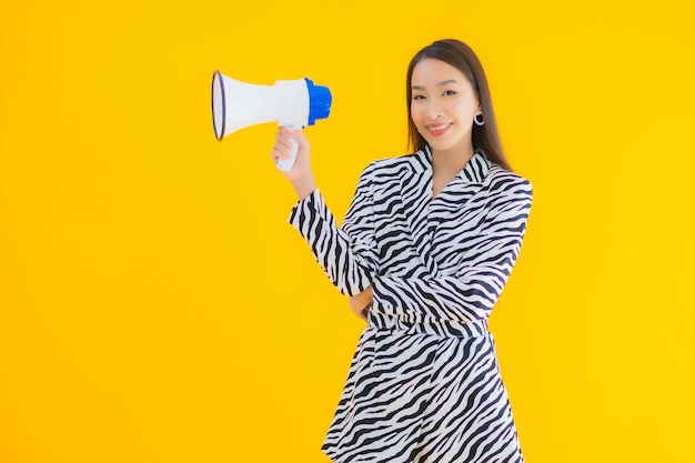 Portrait beautiful young asian woman smile happy with megaphone on yellow