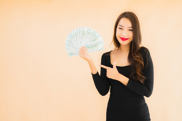 肖像画の美しい若いアジア女性はお金と現金で幸せな笑顔