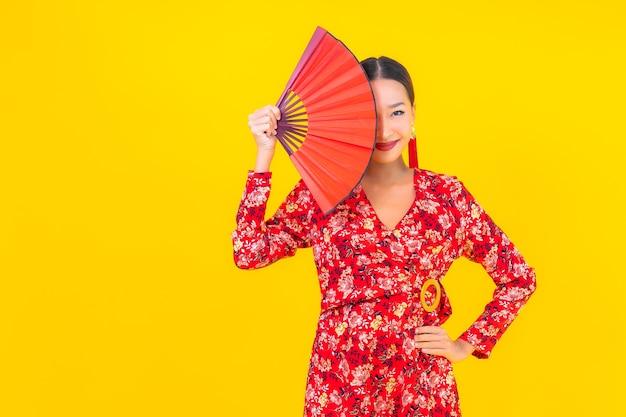色の壁に中国の旧正月のコンセプトでアクションで美しい若いアジアの女性の笑顔の肖像画