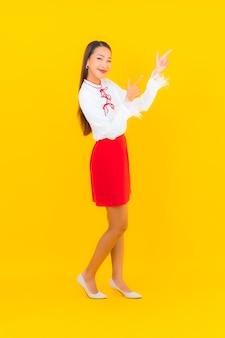 Улыбка женщины портрета красивая молодая азиатская в действии на желтом цвете
