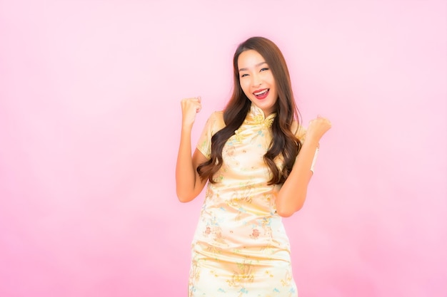 ピンク色の壁に中国の旧正月のコンセプトとアクションで肖像画の美しい若いアジアの女性の笑顔