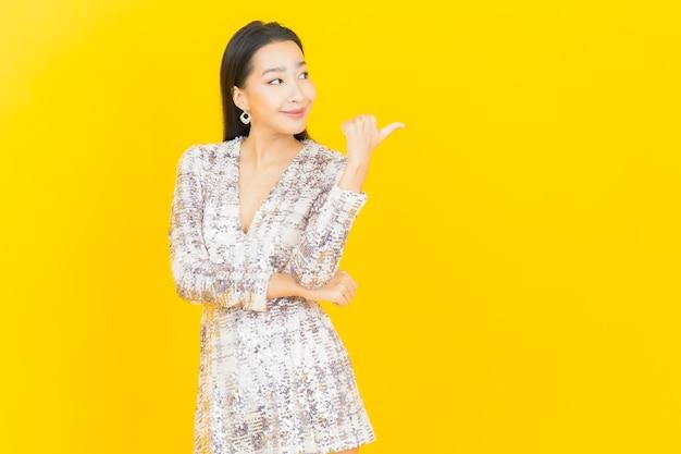 Улыбка женщины портрета красивая молодая азиатская позирует на желтом