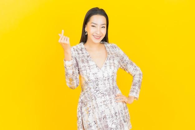 Ritratto di bella giovane donna asiatica sorriso in posa su yellow