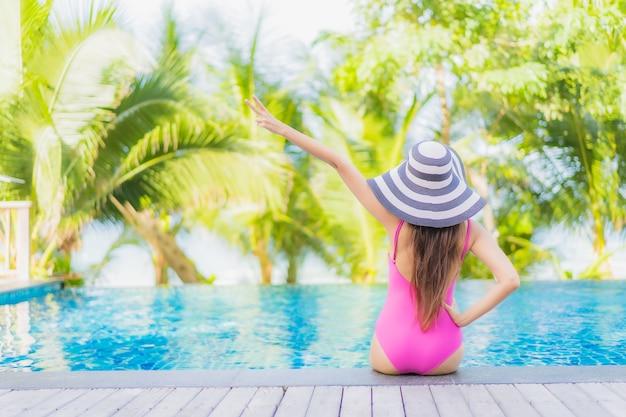 肖像画美しい若いアジアの女性の笑顔は、休日の休暇旅行旅行でリゾートホテルの屋外スイミングプールの周りでリラックス