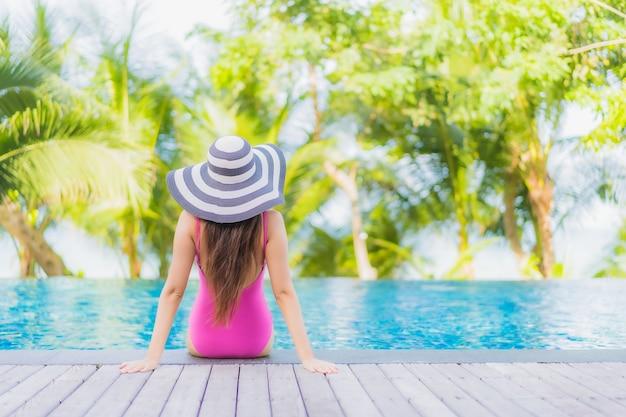 Il bello giovane sorriso asiatico della donna del ritratto si rilassa intorno alla piscina all'aperto nell'hotel della località di soggiorno in viaggio di viaggio di vacanza di festa