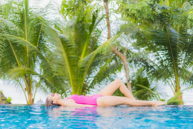 Portrait beautiful young asian woman smile relax around outdoor swimming pool in resort hotel on holiday vacation travel trip