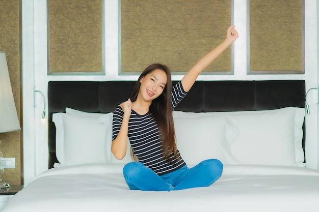 Il bello giovane sorriso asiatico della donna del ritratto si rilassa sul letto nell'interno della camera da letto
