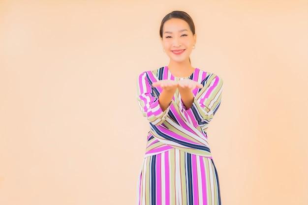 Улыбка женщины портрета красивая молодая азиатская ослабляет в действии на цвете