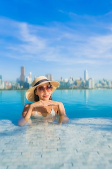 Portrait beautiful young asian woman smile relax leisure around outdoor swimming pool with city view