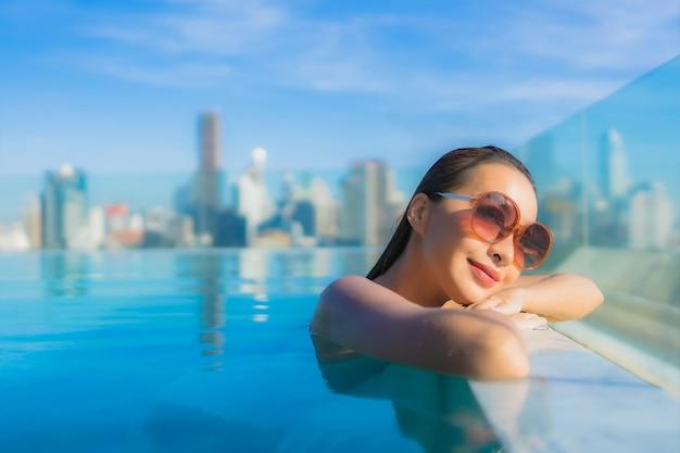 肖像画美しい若いアジアの女性の笑顔は、街の景色を望む屋外スイミングプールの周りのレジャーをリラックス