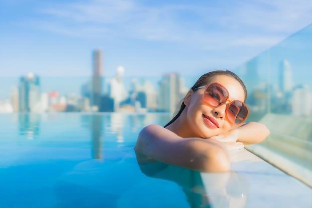 세로 아름 다운 젊은 아시아 여자 미소 도시 전망 야외 수영장 주변 레저 휴식