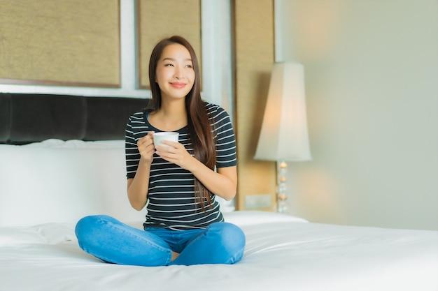 Улыбка женщины портрета красивая молодая азиатская ослабляет на кровати в интерьере спальни