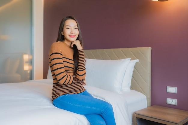 Улыбка женщины портрета красивая молодая азиатская ослабляет на кровати